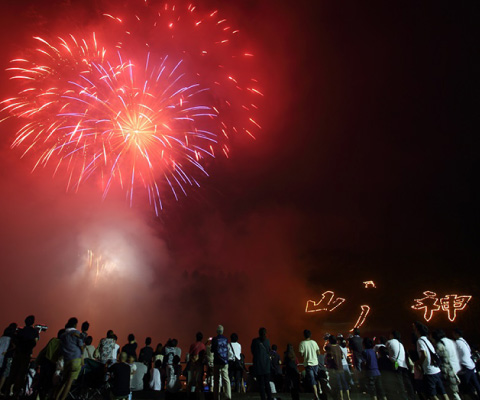 """Colorful fireworks are lighting up the summer night sky above the 3 huge Japanese characters of """"Mountain God"""" written in fire. / Fire festival in Teramura"""